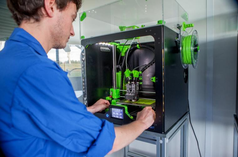 Operator ajusting a 3D printer